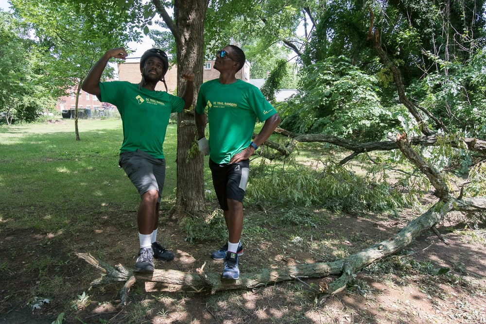 Two men in Trail Ranger shirts posing looking accomplished with a foot on a large tree branch.