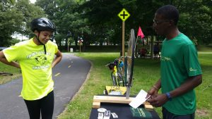A Trail Ranger stands behind a outreach table with lots of materials on it and talks with a teenage trail user with a giant smile. The Anacostia River Trail is behind them.