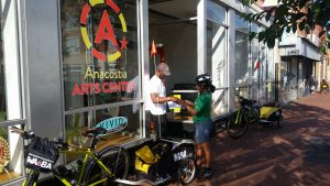 A woman Trail Ranger hands materials to an employee of the Anacostia Arts Center, they are standing outside the front door of the Arts Center and there is a Trail Ranger bike with trailer saying WABA next to the door.