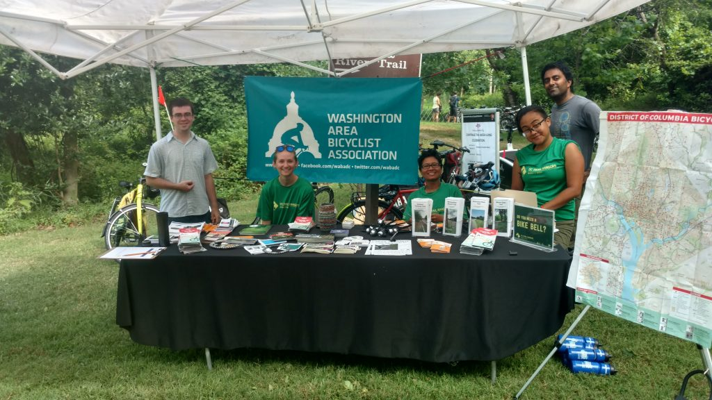 5 people behind a table with lots of outreach material. There is a WABA logo banner behind them, they are under a tent outside on the grass and three of the people are wearing green Trail Ranger shirts. There are 3 men and 2 women.
