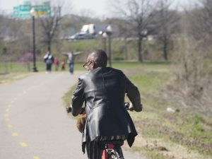Black guy riding a Capital Bikeshare bike and a fancy leather jacket bikes away from the camera in Anacostia park. You can see a few other trail users in the background