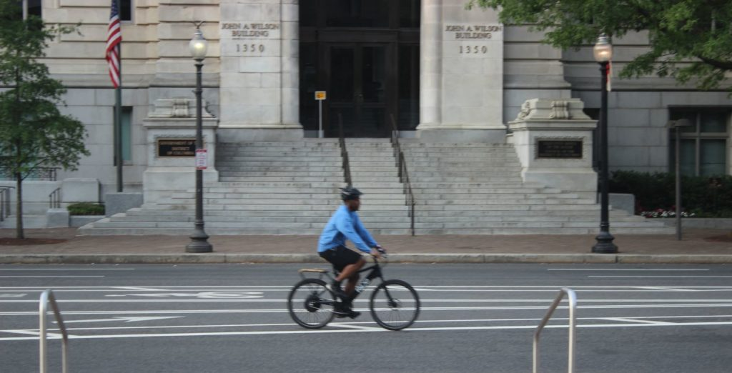 A bicyclist rides in front of the Wilson Building