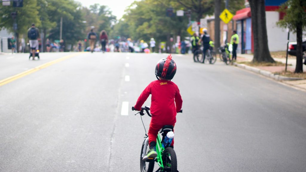 A young person in a superhero costume rides a bicycle down a car-free georgia ave NW during DC's first Open Streets event