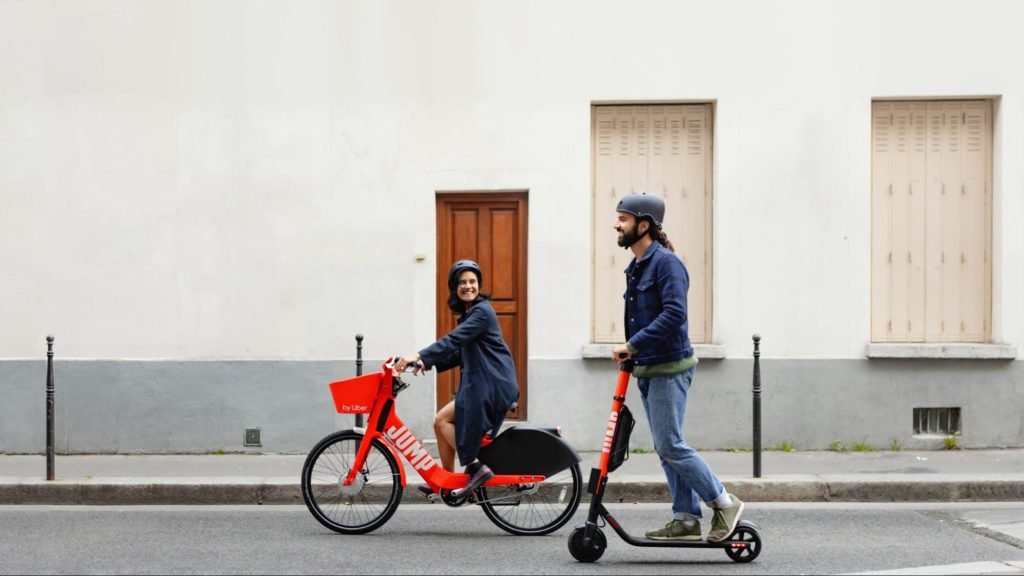 A woman rides a JUMP electric bike and a man rides a JUMP electric scooter. They are  both smiling.