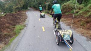 Trail rangers in green shirts ride along the Anacostia River Trail with trailers