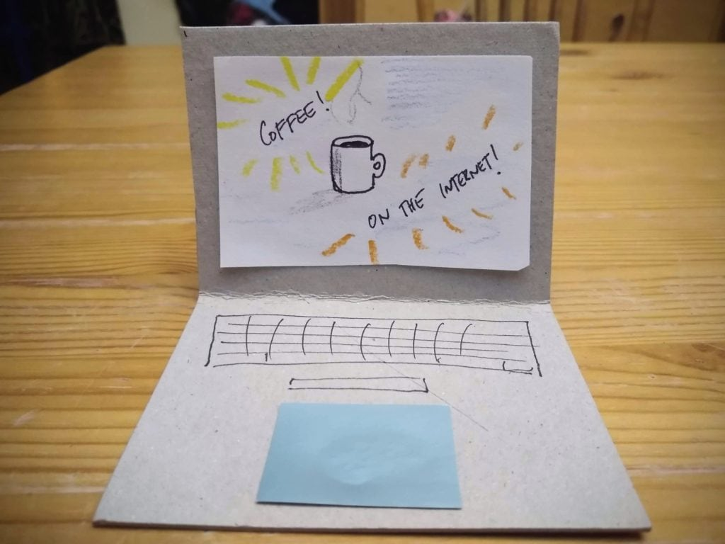 A fake cardboard laptop sits on a table, the screen says Coffee! On the Internet! with a drawing of a mug