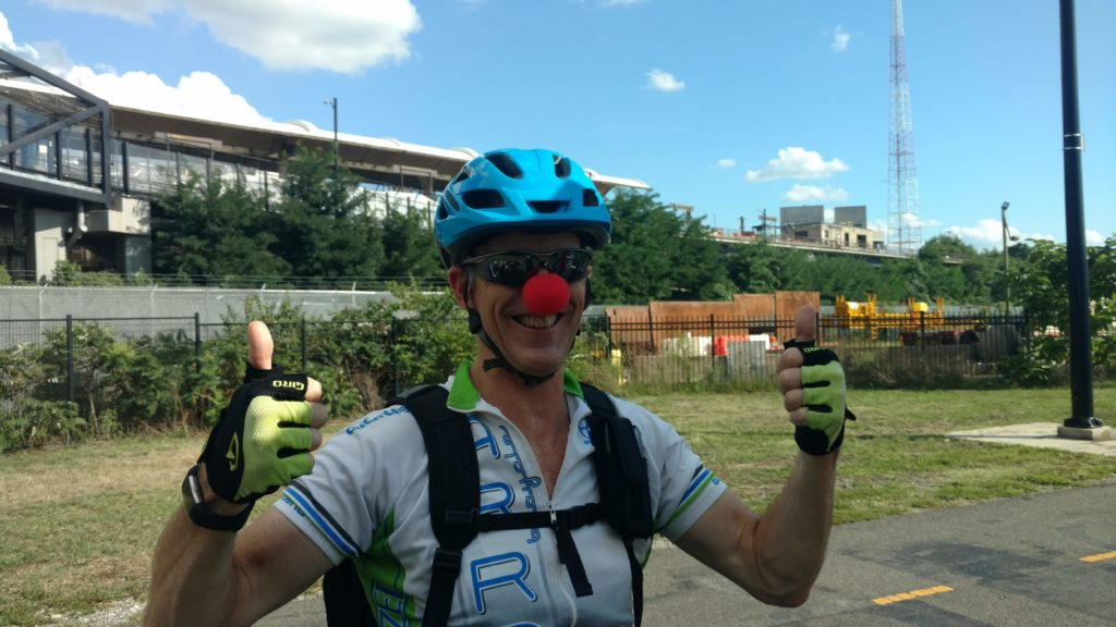 A white guy in spandex wears a red clown nose and a blue helmet and is giving two thumbs up to the camera with a big smile