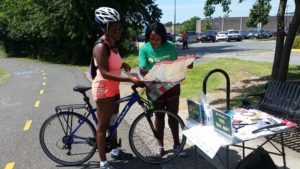 A Black woman trail ranger stands next to a trail holding a map talking to a Black woman on a road bike. It is sunny and the middle of summer.