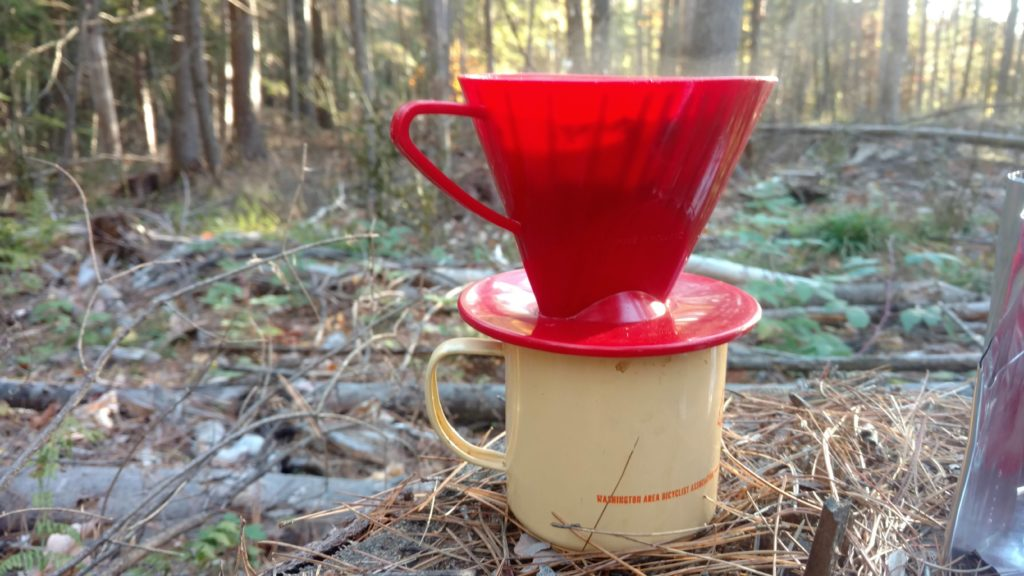 Chipped WABA mug sits on the forest floor with a coffee filter above and steam coming out