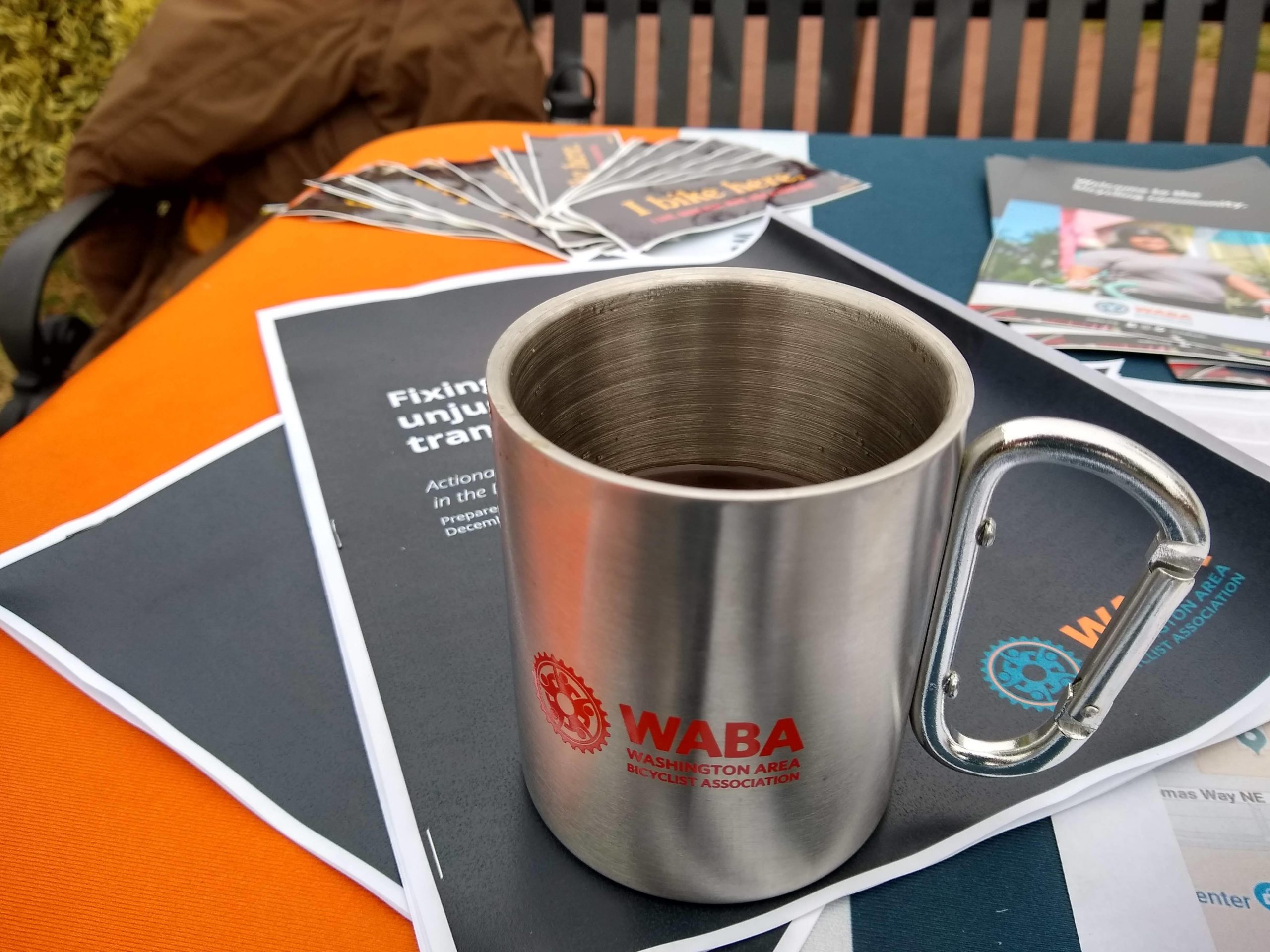 A new metal WABA mug sits on printed docuements that are branded WABA materials on a table outside