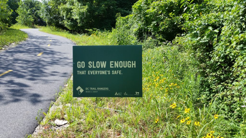 Brightly lit greenery and trail with some black eyed susans and a green yard sign that says Go Slow Enough That Everyone's Safe with the Trail Ranger logo