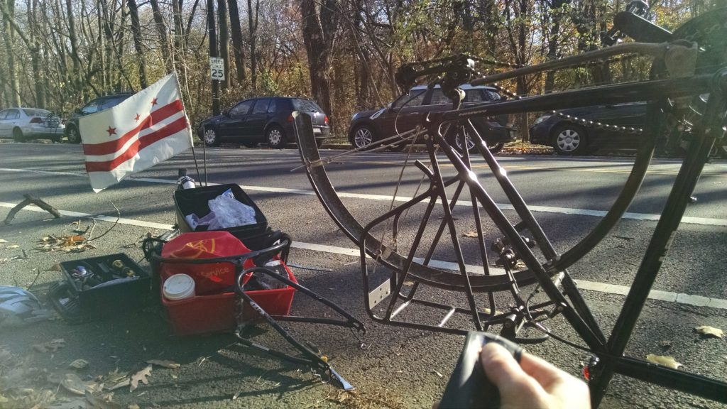 Kinda washed out photo of a back bike wheel missing the wheel, the person is sitting by the road fixing her flat