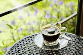 Espresso in a clear glass cup sits on a table, there are lavender flowers behind. It is and looks like a stock photo