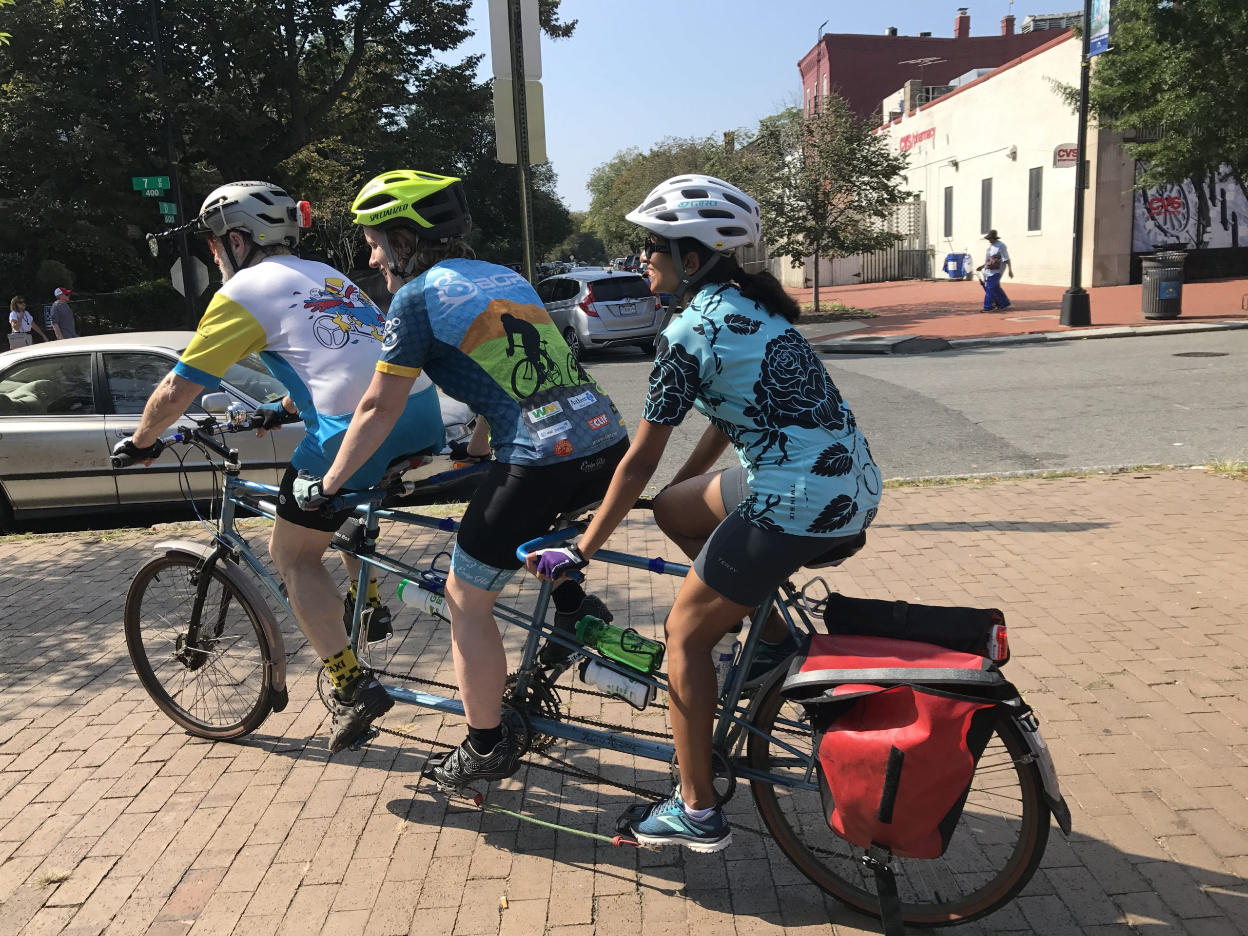 Three people are riding in a line on a three person bicycle away from the camera so you can only see their backs. The captain is wearing a white jersy, and the two people behind are in blue jerseys. Everyone is smiling, the sky is blue and they are about to go for a ride. Photo credit: MWABA