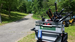 A grey boxes sits on a bicycle and is full of pruner handles. The trail is in the background, and the trees are very green. In the background you can kinda see a Trail Ranger standing in a green shirt