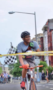 David Confer is riding a bright pink handlebar fixie as he crosses the finish line tape (its actually caution tape) on a road near Union Market area. He is smiling and is an older photo before he got cancer.